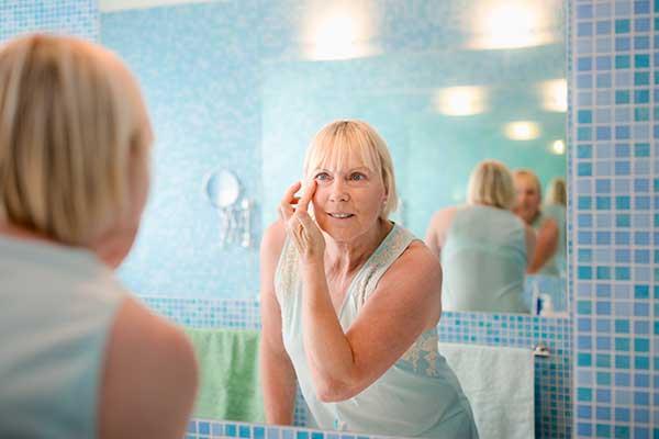 Eine Dame betrachtet ihr  mit Schungit-Wasser gewaschenes Gesicht vor dem Spiegel