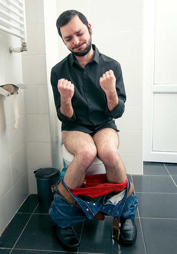 Mann mit Verstopfung auf WC